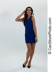 Woman in blue dress posing against white background