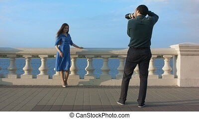 Woman in blue dress posing for photographer.