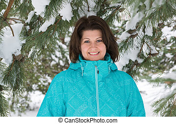 Woman in blue jacket in snow-covered fir forest