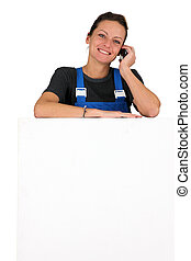 Woman in blue overalls with a cellphone and board left blank for your message