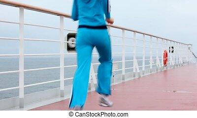 woman in blue runs on deck of floating ship along board