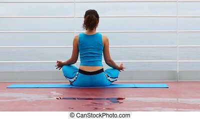 woman in blue sits back in lotus pose on ship deck