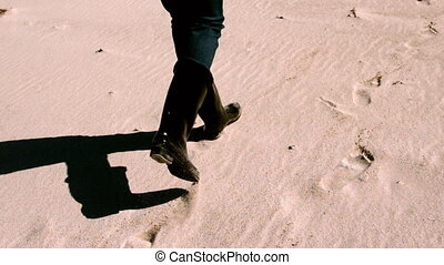 Woman in boots walking on the sand in slow motion