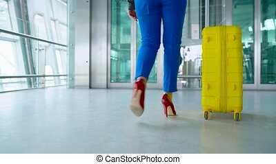 Woman in bright clothes enters the elevator at the airport