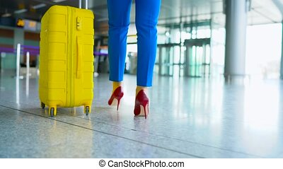 Woman in bright clothes is rolling yellow suitcase in the airport
