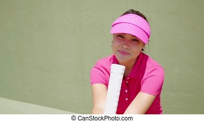 Woman in bright pink shirt and visor while seated near...