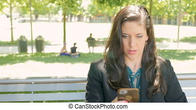 Woman in business clothing texting or emailing on her mobile phone