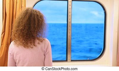 woman in cabin of ship looks out of window on waves