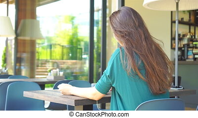 Woman in cafe drinking coffee smiling and listening the music. Beautiful young female professional with mobile phone.