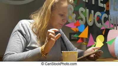 Woman in cafe eating ice-cream and using pad