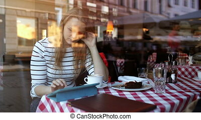 Woman in cafe using tablet PC and eating dessert