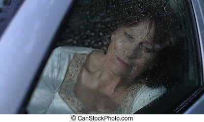 Woman in car look at rain - Melancholy elderly woman look at...