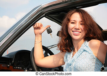 Woman in car shows a key