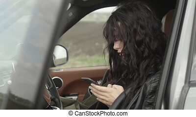Woman in car with smartphone