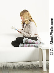 Woman in cardigan reading book sideview