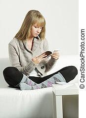 Woman in cardigan reading book