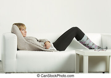 Woman in cardigan relaxed on sofa