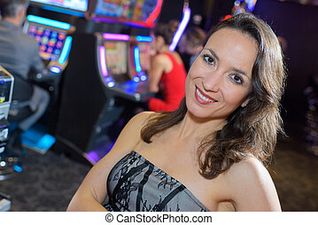 woman in casino next to a slot machine