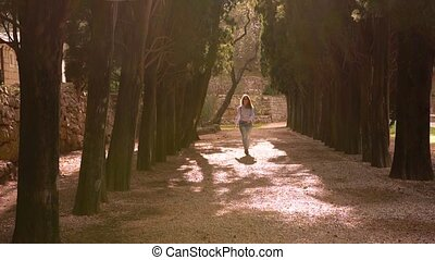 Woman In Casual Clothes Walks Through The Park