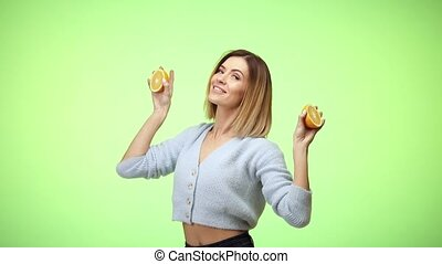 happy smiling beautiful blonde caucasian woman in casual clothes holding oranges and dancing on green color background in studio.