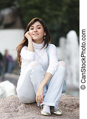 Woman in casual sitting on stone