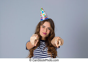 Woman in celebration cap holding pointing fingers - Young...