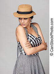 Woman in chequered summer dress and canotier straw hat looking back over shoulder