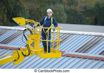 Woman in cherry picker bucket