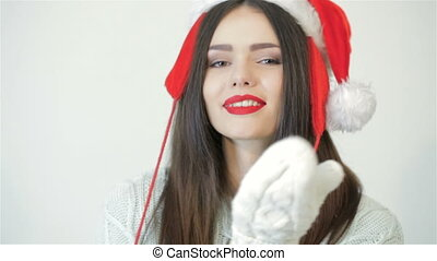 Woman in christmas hat blows kiss.