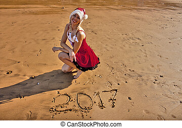 Woman in Christmas hat on the beach with drawing on the sand digits 2017