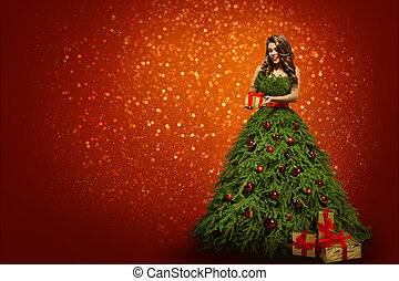 Woman in Christmas Tree Dress Holding Present Gift, Fashion Girl over New Year Red Background