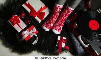 Woman in Christmas warm socks with red and white ornaments sits on a gray fur skin near a retro turntable. Presents, jewelry and tinsel are spread around. Festive mood. Merry christmas and new year. Close up. Slow motion.