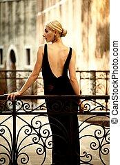 Woman in classic dress on a bridge