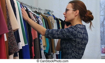 Woman in clothing shop talking with friend with mobile phone and choosing a new dress