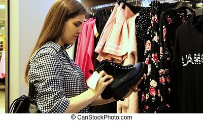 Woman in clothing store chooses shoes