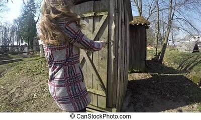 Woman in coat walk into rural wooden wc toilet house in village. Outhouse