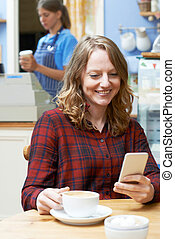 Woman In Coffee Shop Reading Text Message On Mobile Phone