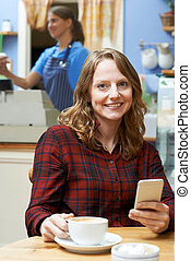 Woman In Coffee Shop Using Mobile Phone