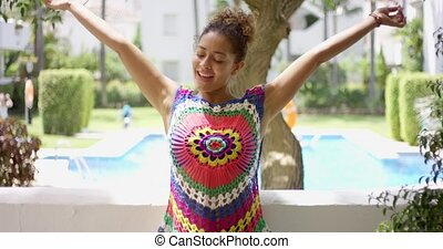 Woman in colorful knit top stretching on balcony - Single...