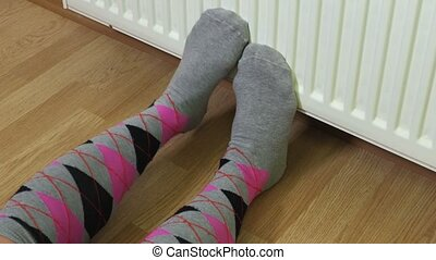 Woman in colorful socks keeping cold feet near heating...