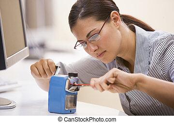 Woman in computer room using pencil sharpener