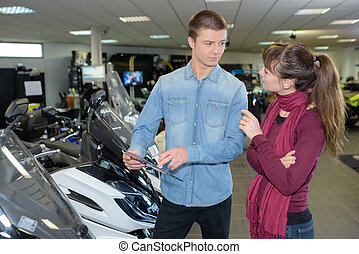 Woman in conversation with salesman in scooter showroom