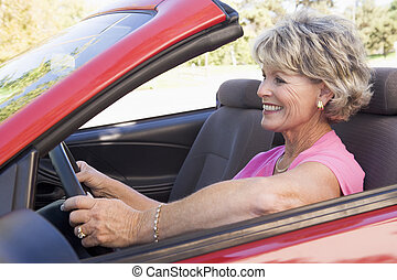 Woman in convertible car smiling