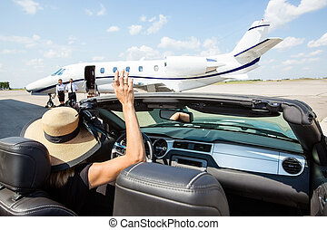 Woman In Convertible Waving To Pilot And Stewardess Against Jet