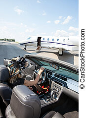 Woman In Convertible With Private Jet At Terminal
