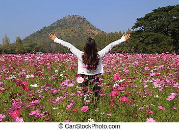 woman in cosmos flower field
