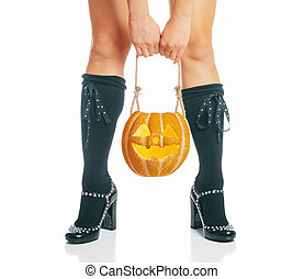 Woman in costume of witch holding carved pumpkin near her legs.