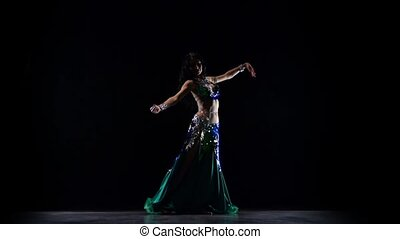 Woman in costume sexually moves her tummy. Black background....