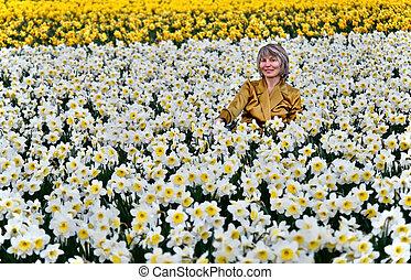 Woman in daffodil fields smiling.