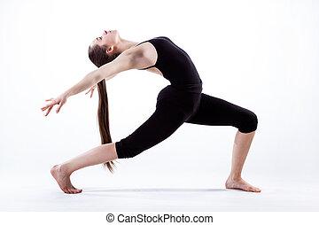 Young flexible woman with long hair making dancing pose